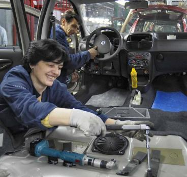 workers putting finishing touches on the last production vehicle
